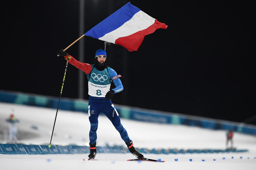 France's Martin Fourcade waves the French flag as he wins the men's 12,5km pursuit biathlon event during the Pyeongchang 2018 Winter Olympic Games in Pyeongchang on February 12, 2018. / AFP PHOTO / FRANCK FIFE